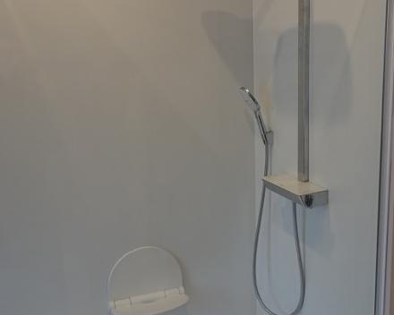 Ergonomisch inklapbaar zitje en douchesysteem met thermostatische kraan, regensproeier en handsproeier.